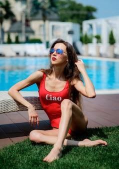 A menina no maiô vermelho senta pela piscina azul