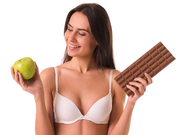 A menina no sutiã branco está prendendo uma maçã e uma barra de chocolate.
