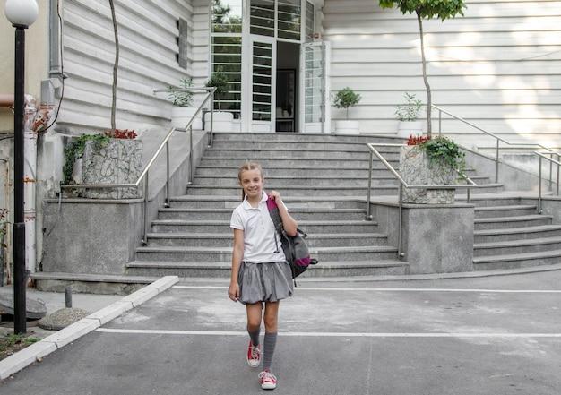 A menina no uniforme anda longe do prédio da escola.