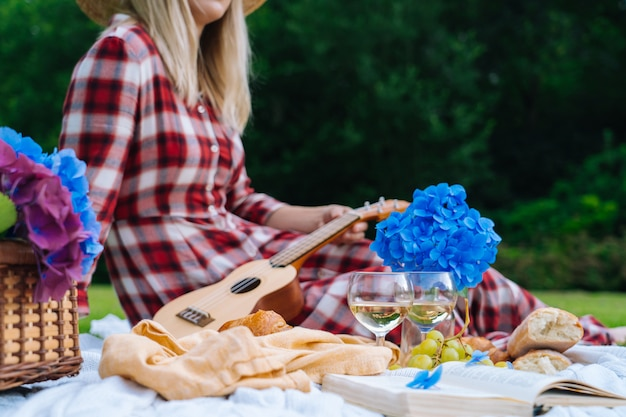 A menina no vestido quadriculado vermelho e no chapéu que sentam-se no cobertor branco do piquenique da malha joga a uquelele e que bebe o vinho. piquenique de verão em dia ensolarado com pão, fruta, flores de hortênsia buquê. foco seletivo