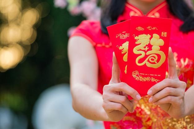 A menina no vestido vermelho de ascendência chinesa está feliz com o envelope vermelho com o dólar.