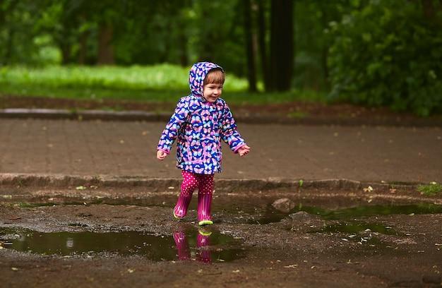 A menina nos gumboots tem o divertimento andar nas associações após a chuva