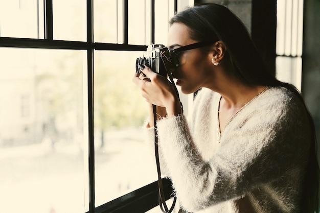 A menina nos óculos leva uma foto diante de uma janela brilhante