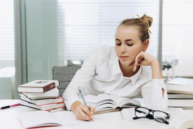 A menina nos óculos trabalha com livros na biblioteca