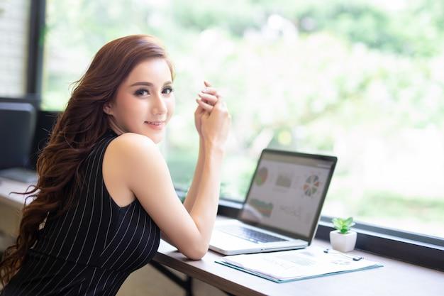 A menina nova asiática do negócio relaxa o trabalho com o portátil no café da cafetaria.
