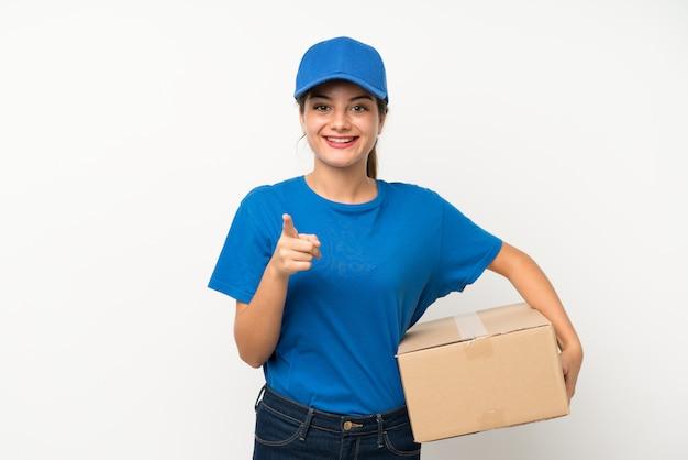 A menina nova da entrega sobre a parede branca isolada aponta o dedo em você
