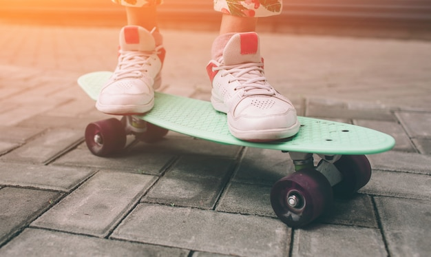 A menina nova do skatista no deslizamento cor-de-rosa nos sapatos monta o skate colorido ao ar livre