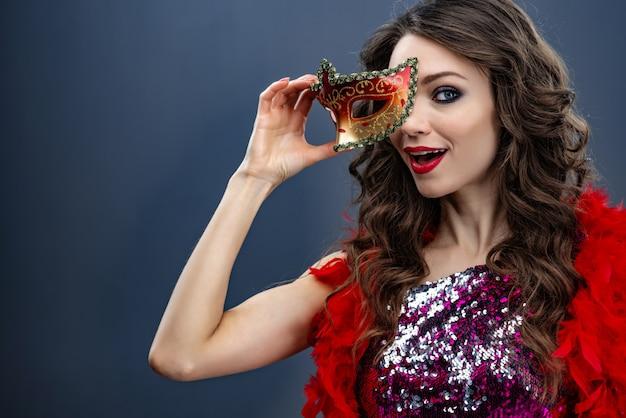 A menina olha divertidamente para a câmera segurando uma máscara de carnaval close-up