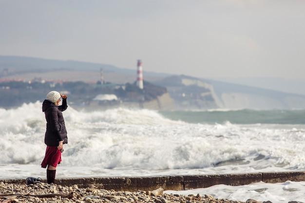 A menina olha para o mar nas ondas de tempestade, ondas de espuma, farol e rochas. a menina está vestida com uma jaqueta preta, chapéu de malha branco, saia longa cor de vinho e botas pretas.