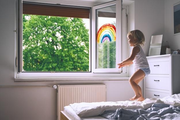 A menina olha pela janela na primavera. criança fofa no fundo da pintura do arco-íris na janela
