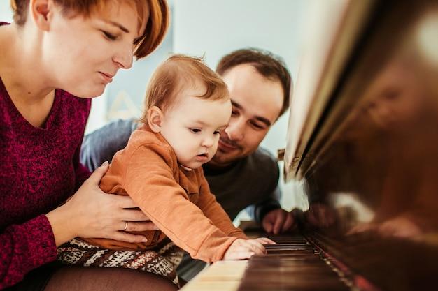 A menina parece engraçada jogando com a mãe no piano