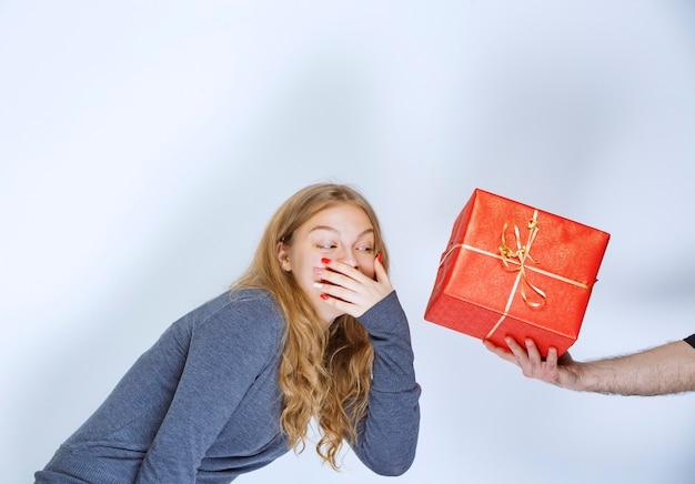 A menina parece surpresa ao ver que uma caixa de presente vermelha está sendo oferecida a ela.