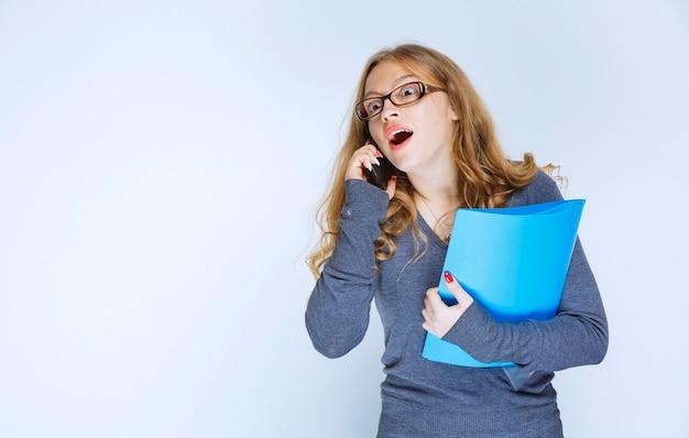 A menina parece surpresa enquanto fala ao telefone e verifica seus relatórios.