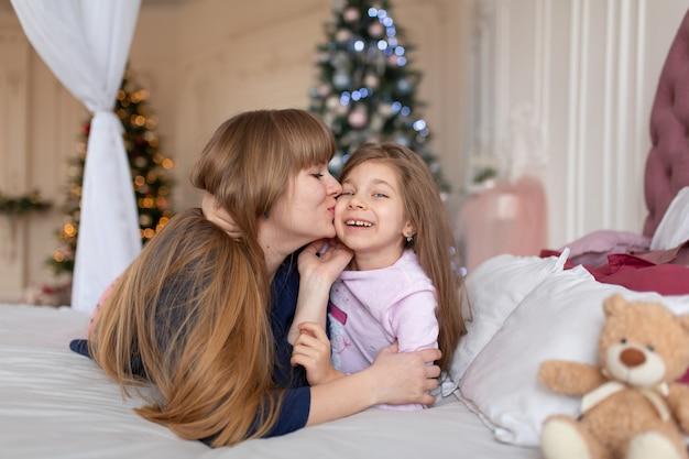 A menina passa o tempo brincando com a mãe enquanto está deitada na cama. conto de natal. infância feliz.