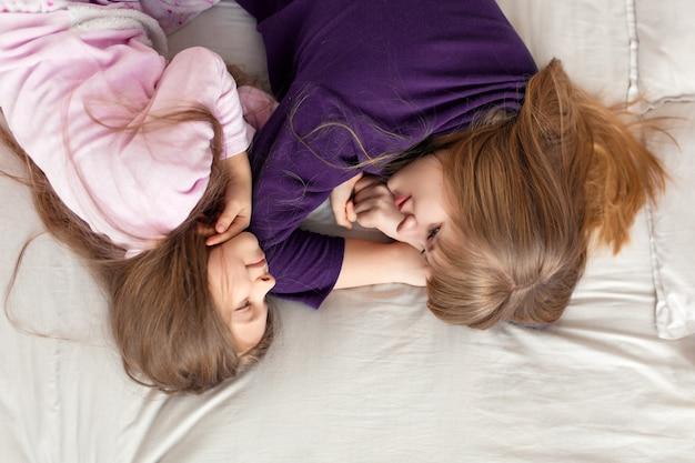 A menina passa o tempo brincando com a mãe enquanto está deitada na cama