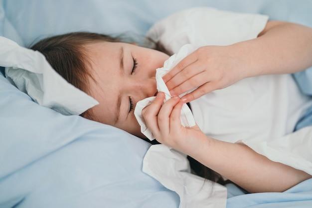 A menina pegou um resfriado. as crianças espirram em um lenço. a criança está doente e está sendo tratada em casa. resfriados sazonais em crianças.