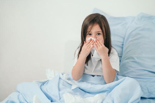 A menina pegou um resfriado. crianças espirram em um lenço. a criança está doente e está sendo tratada em casa. resfriados sazonais em crianças.