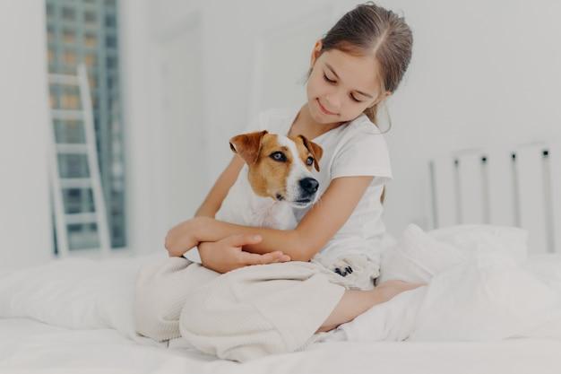 A menina pequena bonita relaxada brinca com cão de raça, abraça o animal favorito