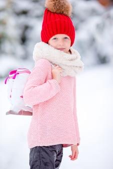A menina pequena bonito da criança está indo fora do patim.
