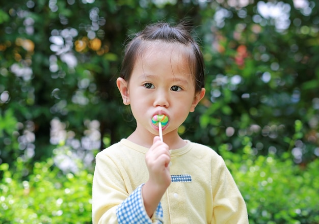 A menina pequena da criança aprecia comer o doce do pirulito no parque
