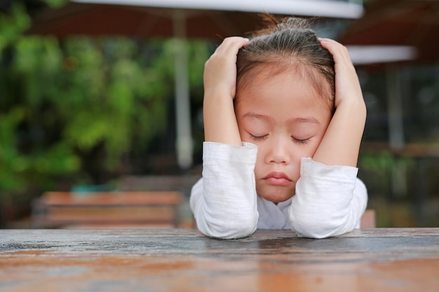 A menina pequena da criança asiática expressou a decepção ou o descontentamento na tabela de madeira.