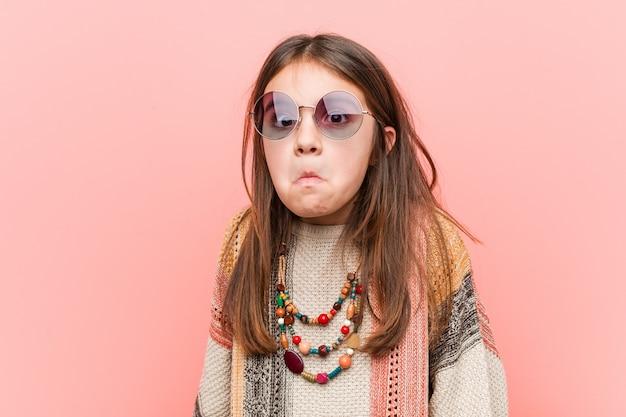 A menina pequena da hippie encolhe ombros e os olhos abertos confundidos.