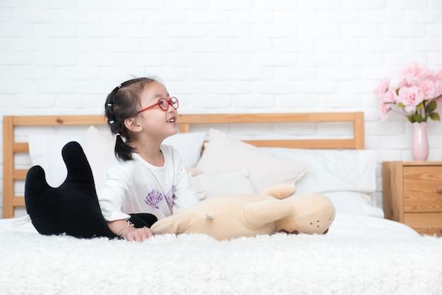 A menina pequena de ásia estabelece na cama com boneca e sorri.