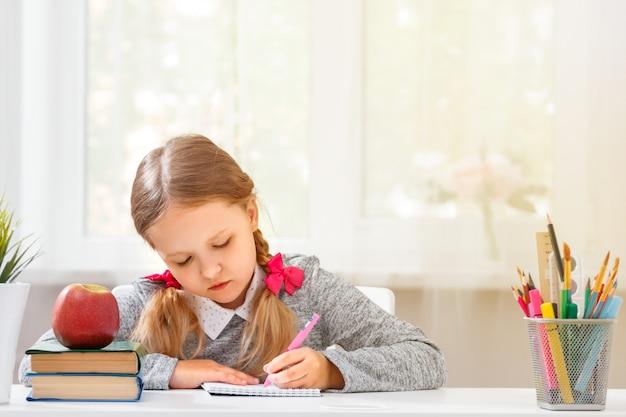 A menina pequena do estudante que senta-se na tabela e escreve em um caderno em um fundo borrado.