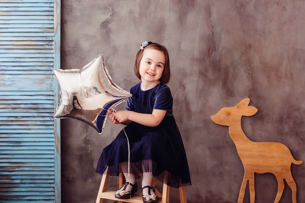 A menina pequena mantem a estrela e senta-se na escada