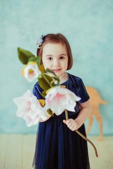 A menina pequena mantem flores no quarto