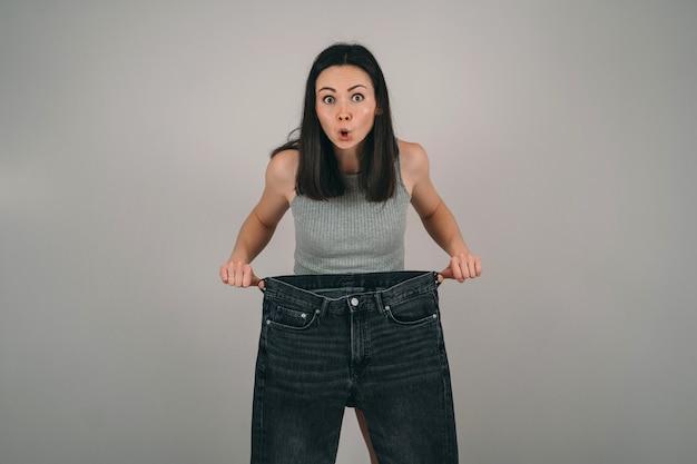 A menina perdeu muito peso. a garota está segurando uma calça jeans muito grande. a mulher fica surpresa com a perda de peso. problemas de anorexia feminina.