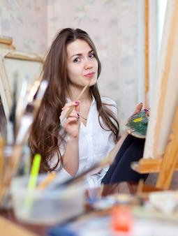 A menina pinta com cores e escovas de óleo