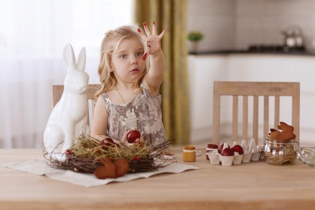 A menina pinta ovos da páscoa na sala na tabela do feriado.