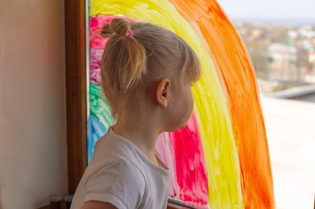 A menina pintou um arco-íris em um close-up do painel de janela.