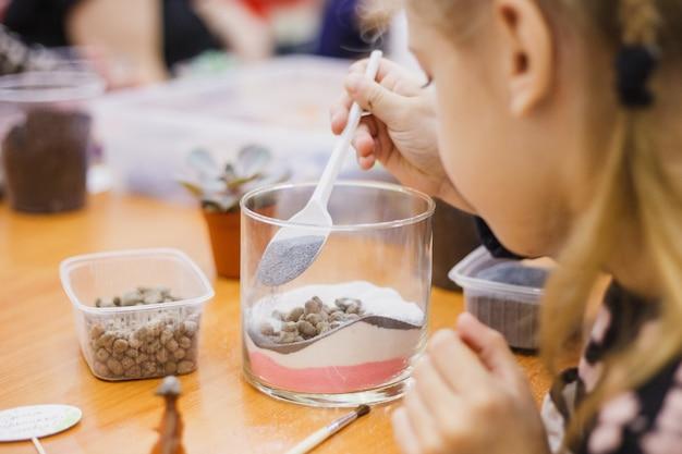 A menina planta uma forma de vidro, plantando flores, vidro terarium