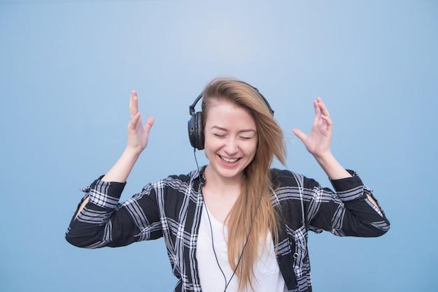 A menina positiva na roupa ocasional escuta música nos fones de ouvido, isolados em um fundo azul.