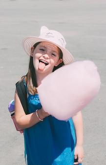 A menina pré-escolar pequena engraçada adorável mostra a língua com floss cor-de-rosa dos doces.