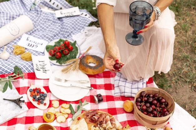 A menina prende cerejas maduras suculentas na mão no contexto de uma manta de piquenique quadriculada com comida espalhada nela