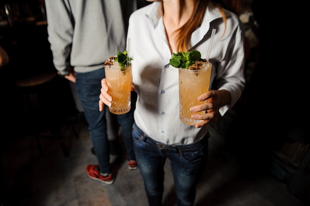 A menina prende dois cocktail alcoólicos alaranjados com gelo, hortelã e canela