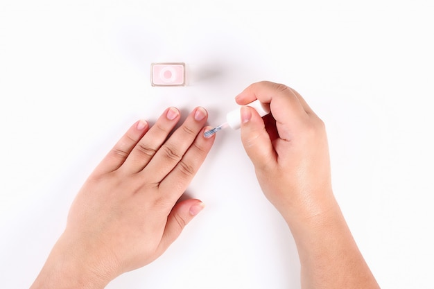 A menina prende em sua mão um verniz para as unhas cor-de-rosa no branco. vista do topo.