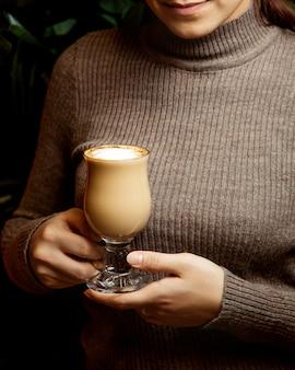 A menina prende o café com leite quente com espuma
