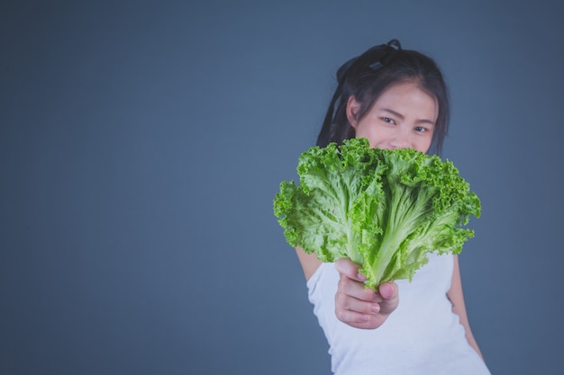 A menina prende os vegetais em um fundo cinzento.