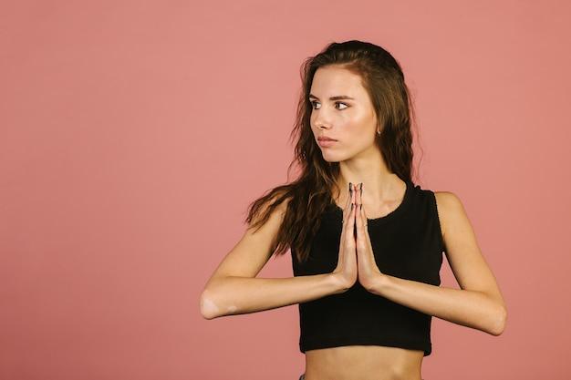 A menina prende suas palmas são dobradas na frente de seu peito para a oração