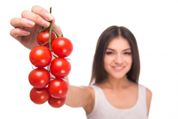A menina prende tomates nas mãos e sorri.
