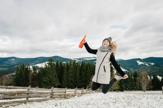 A menina pula no inverno nevado, anda na natureza.