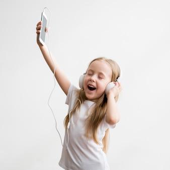A menina que aprecia a música joga fones de ouvido