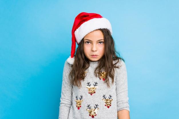 A menina que comemora o dia de natal encolhe os ombros e abre os olhos confusos.