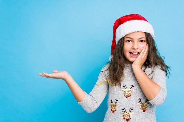 A menina que comemora o dia de natal guardara o espaço da cópia em uma palma, mantenha mão sobre a bochecha. espantado e encantado.