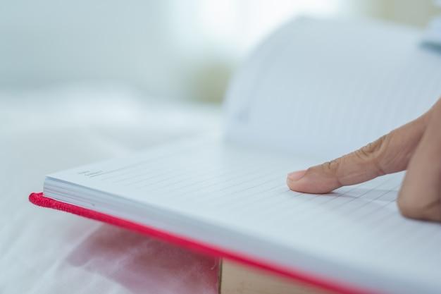 A menina que encontra-se na cama que escuta a música e que lê livros.