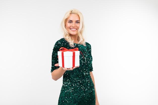 A menina que joga feliz em um vestido verde brilhante recebeu um presente de aniversário em um fundo branco com espaço da cópia